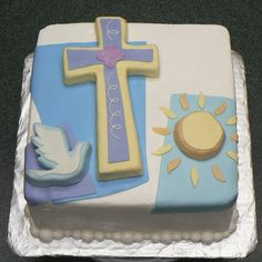 a first communion cake made to match the napkins and plates with carved 3D pieces, a dove, a cross and a sun