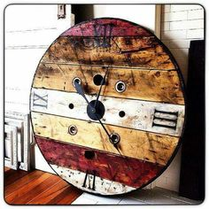 Rustic wood clock from cable spool holder. Stain slats different colors? Wish I could find original link. This clock is awesome! Industrial Clocks, Rustic Wall Clocks, Wood Clocks, Wooden Cable Spools, Wood Spool, Huge Clock, Spool Tables, Sewing Tables, Spool Crafts