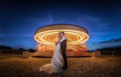 Preston Court Wedding Photography. Couple in front of the beautiful fairground carousel. A wonderful wedding venue in Canterbury, Kent.