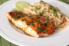 Asian Glazed Salmon    2 salmon filets  2 tablespoons ginger-sesame sauce   1 tablespoon soy sauce  squirt of fresh lime juice  1 teaspoon brown sugar  cilantro  Preheat oven to 400 degrees. Place the salmon filets, skin side down, on a baking sheet lined with greased foil. Brush with half of the marinade and bake for 10 minutes. Brush with remaining marinade and return to oven for 10 minutes more until salmon is cooked through. Serves 2.