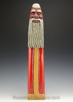 """A very tall, 23 inch Black Santa Claus with deep, cherry red coat and gold trim. This Santa has beautiful brown eyes and a long curled beard. Designed, carved out of solid and aged redwood, painted, finished and signed by Paul Green."""