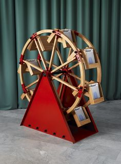 The idea for 'The Wheel' came to American designer Vladimir Kagan during a trip to London, where he noticed that the London Eye's shape would make a perfect rotating home for magazines. Standing on a red metal base, the rack is made of solid oak and metal and can turn in both directions. #wallpaperhandmade