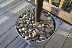 DIY Umbrella Stand...Fill a galvanized bucket with large pieces of limestone or chunks of concrete to weigh it down.  Then, use some river rocks to fill the rest of the bucket up and make it look pretty.  Those stands are so costly at the stores; this one costs maybe 5 dollars or less to make.  :)