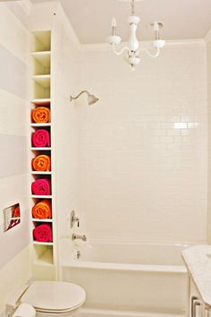 What a great idea for finding storage space in a tiny bathroom - and the graphic, colourful quality of the rolled towels adds artistic impact to an all white scheme.