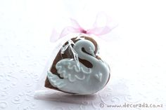 Swan bridal cookie.  Gingerbread heart shape biscuit with royal icing swan, feather and heart detail.