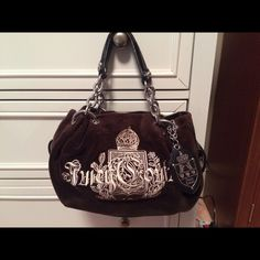 """Black Authentic Juicy Couture Handbag This is a used authentic juicy couture handbag. There are two small magnetic flap pockets on the outside, and the inside has two pockets. Inside is also a narrow silver strap with the words """"I am the fairest"""" with a detachable heart shaped mirror. Note the picture of the mirror and small scratch where silver has peeled off. Also note the wear on the handles. Juicy Couture Bags Shoulder Bags"""