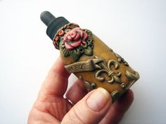 Victorian Rose bottle with dropper covered in polymer clay handmade by Marie Segal. $19.99, via Etsy.