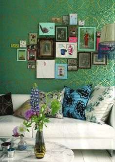 Green and gold wallpaper as a background for the colors in the frames. Purple flowers.  White floors and furniture.