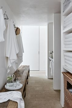 White towels and linens hanging in a hallway complement the pool house's neutral palette. #naturaldecor #poolhouse
