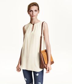 Sleeveless blouse in woven fabric with a metal decoration at neckline. Opening at back of neck with concealed button. Rounded hem, slightly longer at back.