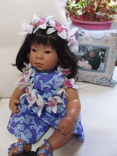 Lee Middleton Hawaiian doll, notice the photo on the pillow is me with a real doll, my granddaughter Tikvah. I designed the pillow while doing tapestry work for Weavetec Simply Home.