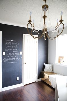 gorgeous home office with walnut laminate flooring and blackboard accent wall a gold trunk topped with gray accent pillow and throw sits below the window beautiful home office chalkboard