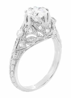 Edwardian Antique Style 1 Carat Diamond Filigree Engagement Ring in 18 Karat White Gold -  R6791D -   Hand crafted in 18K white gold, this gorgeous 1 carat Edwardian filigree diamond engagement ring features a stunning white & bright 1.00 carat GIA graded diamond.  Delicate filigree, milgrain edging, bows, & diamond set flowers adorn the setting, embedded with white round brilliant cut diamonds.  The band of the ring is engraved with an Art Deco wheat pattern, symbolic of an abundant…