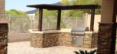 Specially designed pergola cuts the sun's glare on this built in grill. Glendale, AZ natural stone grill island and paver patio with outdoor fire pit by Desert Crest. Backyard Kitchen, Outdoor Kitchen Design, Patio Design, Backyard Patio, Flagstone Patio, Patio Wall, Outdoor Kitchens, Outdoor Cooking Area, Grill Island