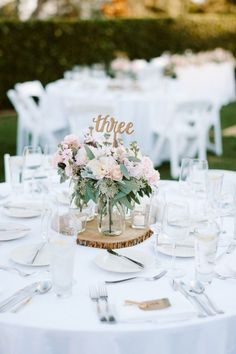 Whimsical and Romantic spring wedding centerpieces - rose flower arrangement for a white pink rose gold color scheme outdoor wedding ceremony venue