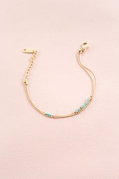 Delicate, double layered gold bracelet adorned with tiny turquoise beads.