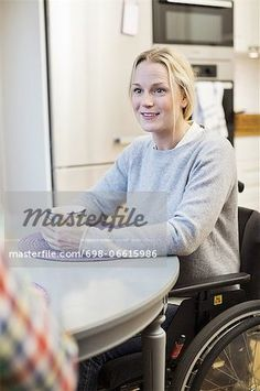 Disabled mid adult woman in wheelchair looking at friend in kitchen  – Image © Masterfile.com: Creative Stock Photos, Vectors and Illustrations for Web, Mobile and Print