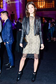 Jacquelyn Jablonski wears a leather jacket over a lace slip dress with cut-out black ankle boots