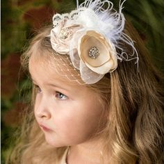 The Penelope vintage rosette headband features one handmade, satin rosette and one stunning hand-singed satin and taffeta flower along with ivory English lace, feathers and birdcage netting.