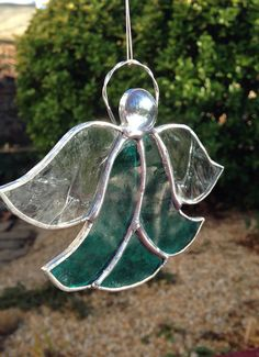 Stained Glass Teal Angel. Made with a clear teal textured glass with clear textured glass for wings. Copper foiled and silver soldered with a clear glass nugget for face. Measures approx. 4x 4 from bottom of Angel to top of halo. Polished and ready to ship. Makes a beautiful gift, ornament