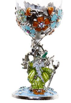 """Draco is enameled dark green with light green wings. The petite goblet is silvertone with hand enameled flowers with aurora borealis crystal centers and the base is enameled a light blue.  Silvertone base  Glass is fixed and does not unscrew   Measures approximately 5""""H x 2""""W"""