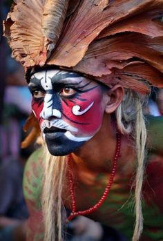 A Polynesian warrior in full head dress and face paint