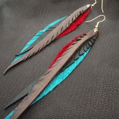 Long feather earrings made of hand cut leather. A great summer accessory in a hot colour combination - the dissonant energy created by teal and red is grounded by rustic brown and flat black. Each pair is custom made to order. Feel free to make requests regarding colours and lengths. The beautiful shape is flattering to your face and the length of the earring is also stunning with an up-do or peeking out from under long hair.  Unlike conventional feather earrings, these wont get messed up…