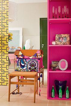 A estante na cor pink acompanha o tom da viga neste apartamento assinado pela arquiteta Andrea Murao. Ao lado, o espelho amplia a sala, que tem piso e paredes em tons neutros