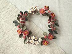 刺繍糸を細いレース針でていねいに編んで作った、つばき、うめ、なんてんの、お正月のリースです。小さな白い梅の花、まるくて赤い南天の実。落ち着いたピンクの椿は、濃淡の2色です。お正月らしい花と実を集めて作った、はなやかで和風なリースです。花や実のひとつひとつを、刺繍糸をかぎ針編みし、ワイヤーに巻き付けて形作りました。リースの土台も、ワイヤーに麻混の糸を巻いて、作っています。※12月25日の上賀茂手づくり市に展示するために制作したものですので、発送は展示して後、26日以降となります。年内には間に合うと思いますが、どうぞご了承ください。m(_ _)m※できるだけていねいに制作しておりますが、手づくりの作品ですので、既製品ほどの強度、完成度はありません。どうぞ、ご理解の上、ご購入ください。m(_ _)m※ワイヤーが入っているので、あるていど形を変えることができます。なるべくねじらないようにお願いいたします。※型くずれした場合は、アイロン用スプレー糊などを付け、手で形を整えて、ドライヤーで乾かすか自然乾燥させてください。※気になる点などございましたら、お気軽にお問い合わせください。