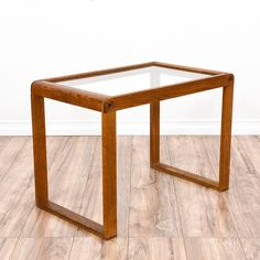 This modern end table is featured in a solid wood with a medium toned oak finish. This side table is in good condition with a durable glass table top, simple straight legs and a sleek design. Perfect table fit for any space! #modern #tables #endtable #sandiegovintage #vintagefurniture