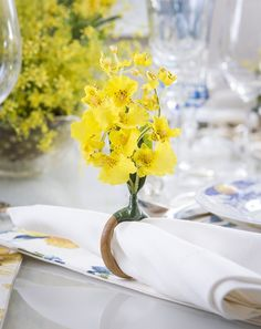 Para completar a mesa, guardanapos em linho branco, porta-guardanapos chuva-de-ouro, talheres em prata, descansos de talher e marcadores de lugar também em prata.