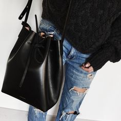 Used-look blue jeans in boyfriend style, black pullover, black leather bag.