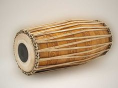 Mridangam. The mridangam is one of the most popular classical instruments of South India. Mridangam accompanies vocal, instrumental and dance performances. The present day mridangam is made of a single block of wood. It is a barrel-shaped double-headed drum, the right head being smaller than the left. The two heads are made of layers of skin. The mridangam is played with hands, palms and fingers.