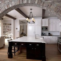 Beautiful open concept kitchen with brick archway, light marble counter-tops and white cabinets.