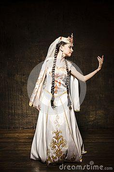 Belle danse de fille dans le studio dans la robe blanche nationale