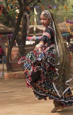 Female kalbelia dancer in traditional tribal dress performing at the annual Sarujkund Fair near Delhi, India photo