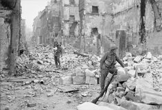 A British soldier carries a little girl through the devastation of Caen. July, 1944.
