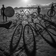 natgeo - Photo by @dguttenfelder. Brazilian men kick a ball over a makeshift net made of bicycles lined up on the beach in Santos, Brazil.