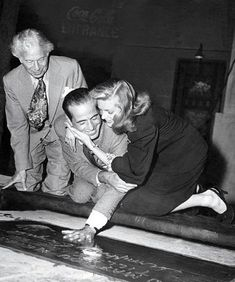 Sid Grauman looks on as Humphrey Bogart gets a little help from Lauren Bacall to immortalize his handprint in front of The Chinese Theatre (1946).