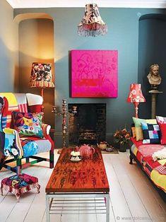 sala decorada no estilo boho chic, bohemiam chic com sofá e poltrona em patchwork, parede asul com quadro rosa