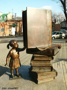 Taganrog. Library named after Anton Chekhov.  Jan. 27, 2010 opening of the new building of the Central City Public Library. Before the new building meets readers bronze sculpture - a girl, extending out to a pile of books.