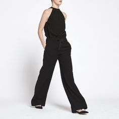This wide-leg jumpsuit's pleated halter top, waist-defining construction, and…
