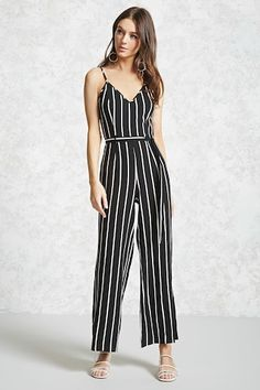 Style Deals - A woven cami jumpsuit featuring an allover pinstripe print, adjustable cami straps, a V-neckline, tie-waist, wide legs, and a concealed side zipper.