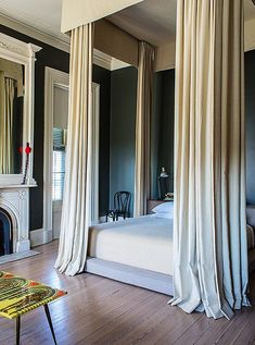 Design idea: Make ceilings look sky high with a low bed on the floor and dramatic glamorous curtains on the four post canopy bed to draw the eye upward. : canopy-bed-studio-apartment - designwebi.com