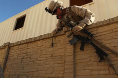 A Marine with Company K, 3rd Battalion, 5th Marine Regiment, scales a wall to get to the squad's objective during a counter insurgency exercise at the Combat Center's Range 215, Nov. 18th, 2013(Official Marine Corps photo by Lance Cpl. Charles J. Santamaria/Released)