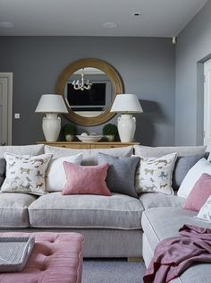 Grey walls and sofas with pink accents work beautifully together in this stylish farmhouse living room