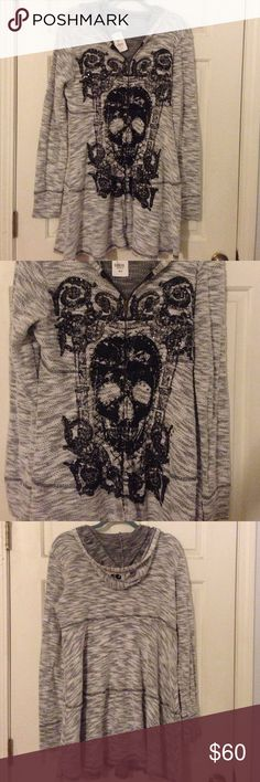 ~*Vocal brand skull bling studded sweater hoodie~* This is absolutely gorgeous!! It is a thin sweater like material and it zips up and has a hood. Would look stunning with leggings or skinny jeans and boots. It has shiny studs and the hood also had skulls on the back of it. It's brand new and I purchased it at a boutique in Vegas but never got a chance to wear it. It could fit a large-extra large. Vocal Sweaters