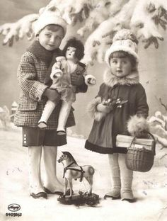 1920s: two beautiful children pose for a Christmas postcard photo. Big Brother holds a bisque doll, whose hair - like Little Sister's - reflects the contemporary trend for cropped 'flapper bob'...