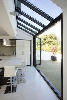 Une large baie vitrée pour faire entrer la lumière et la chaleur dans votre maison. Composée en aluminium et de couleur noire, elle rappelle les verrières d'antan. Sa porte-fenêtre permet de passer facilement de votre maison à votre terrasse.