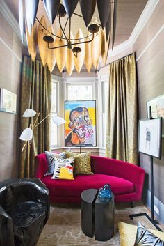 A vintage curved sofa upholstered in rich red velvet provides a perch for sipping cognac and admiring art in this vibrant study. - Photo: Brittany Ambridge / Design: Michel Smith Boyd